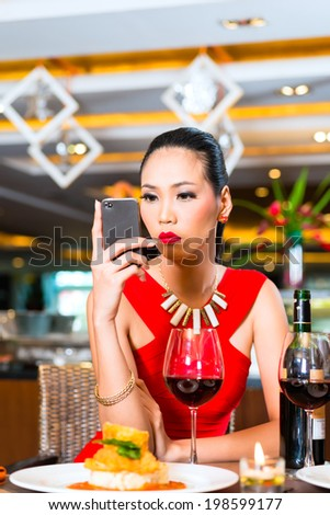 Young woman sitting in restaurant with mobile phone