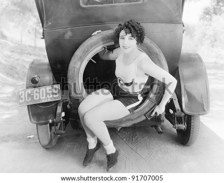 Young woman sitting in the extra wheel of a car - stock photo