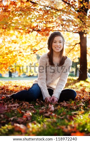 Young woman sitting in the leaves enjoying fall - stock photo