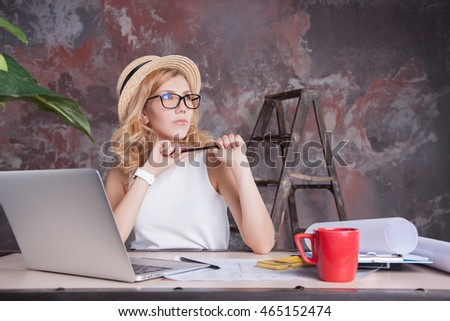 Young woman sitting in the office and working on laptop. Eastern European Business Woman, working in New York. the girl behind the desk in his office, working on laptop computer. Copy Space.