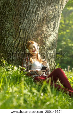 Young woman sitting in the park and listening the music from a smart phone - stock photo