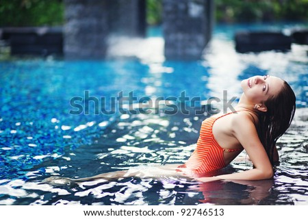 Young woman sitting in the pool in luxury resort, Bali, Indonesia - stock photo