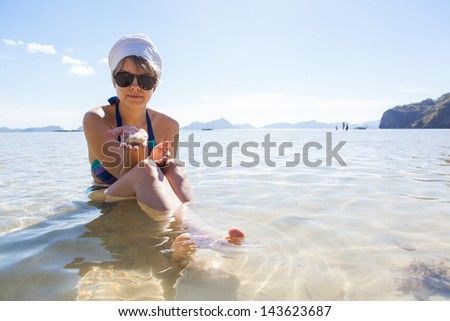 Young woman sitting in water holding a seashell