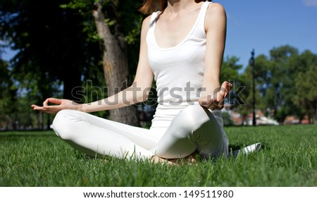 young woman sitting  in yoga pose in green park, closeup - stock photo