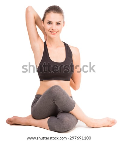 Young woman sitting in yoga pose, looking at camera and smiling. - stock photo