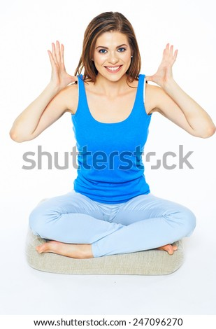 Young woman sitting in yoga pose on a floor. Smiling model with long hair isolated sport portrait. - stock photo