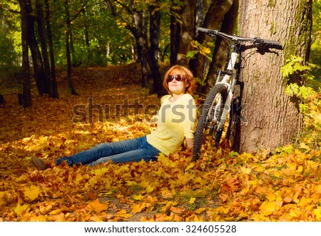 young woman sitting near bicycle in park