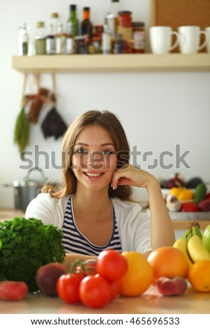 Young woman sitting near desk in the kitchen