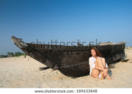 Young woman sitting near the black wooden boat  - stock photo