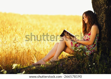 Young woman sitting near wheat field, reading.
