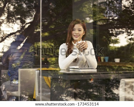young woman sitting next to windows in cafe. - stock photo