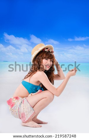 Young woman sitting on a beach and enjoying the sun - stock photo