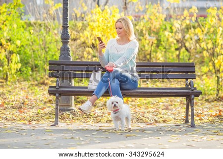 Young woman sitting on a bench and using mobile phone while walking her dog in a park - stock photo