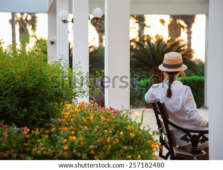 Young woman sitting on a bench at sunset - stock photo