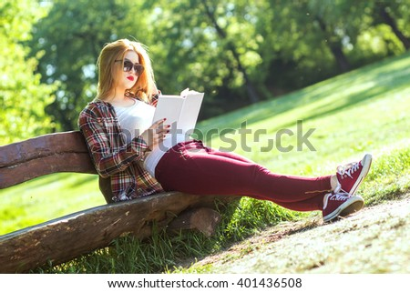 Young woman sitting on a bench in the park and reading book - stock photo