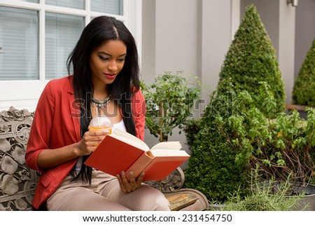 young woman sitting on a bench reading a book with a smoothie - stock photo