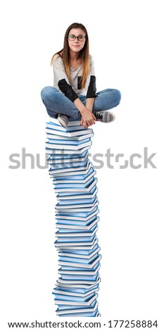 young woman sitting on a books tower isolated on white - stock photo