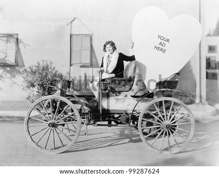 Young woman sitting on a car holding a big heart shaped sign - stock photo