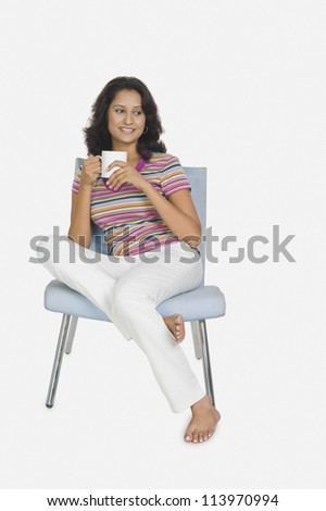Young woman sitting on a chair and drinking tea - stock photo