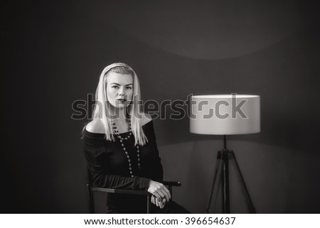 young woman sitting on a chair in the studio floor lamp red lips lipstick look a serious sadness black and white psychology