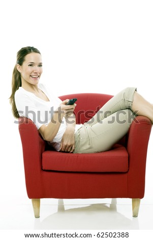 Young woman sitting on a chair with remote control on white background studio