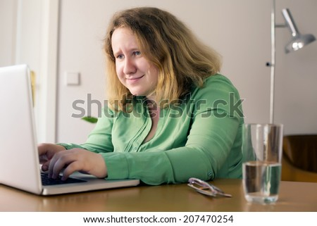 young woman sitting on a desk with laptop and looks stressed