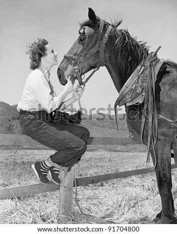 Young woman sitting on a fence and feeding her horse - stock photo