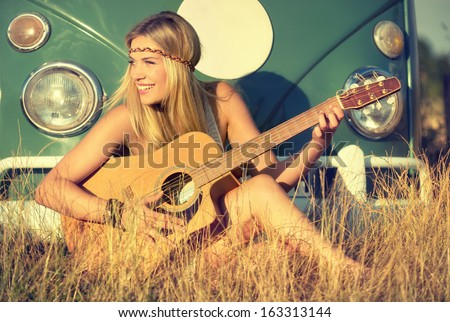 young woman sitting on a field and playing guitar - stock photo