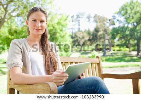 Young woman sitting on a park bench with her tablet computer