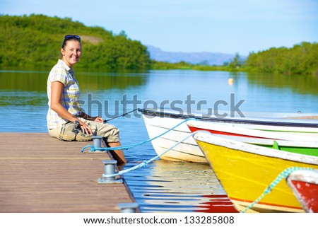 Young woman sitting on a pier. Lake in Asbyrgi area of Jokulsargljufur National Park of Iceland - stock photo