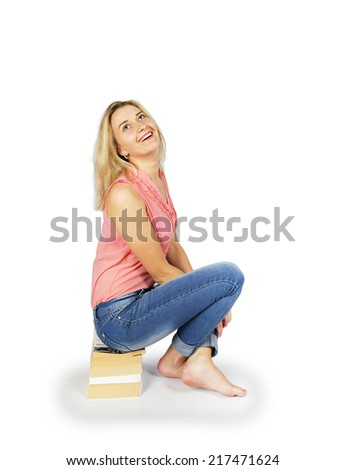 Young woman sitting on a pile of books isolated on white background - stock photo