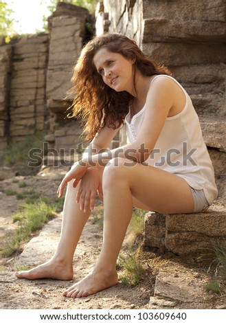 Young woman sitting on a rock