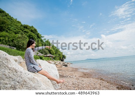 Young woman sitting on a rock enjoying the sea view on the beach