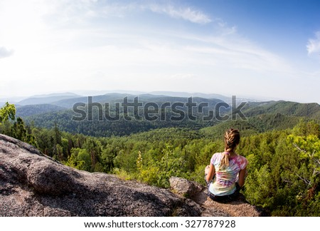 Young woman sitting on a rock, looking to the horizon
