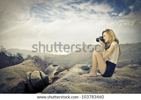 Young woman sitting on a rock on a hill and taking pictures with a camera - stock photo