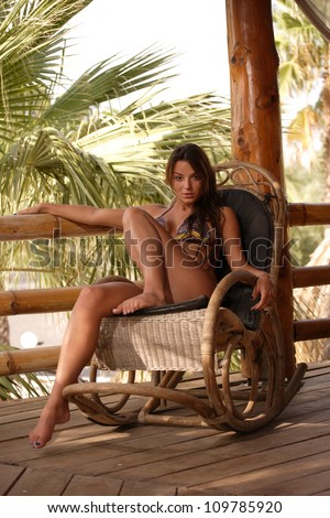 Young woman sitting on a rocking chair at tropical resort - stock photo
