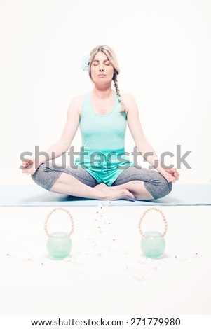 Young woman sitting on a rug on the floor in the lotus position meditating with her eyes closed and a peaceful expression as she does her yoga exercises to relax her mind and body - stock photo