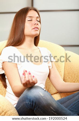 Young woman sitting on a sofa in the lotus position meditating - stock photo