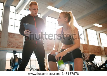 Young woman sitting on a stool and discussing exercise plan with personal trainer. Trainer making an fitness plan for young female client at gym. - stock photo