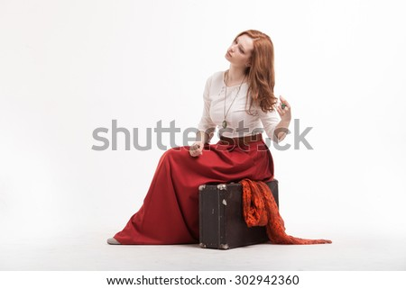 Young Woman sitting on a suitcase, isolated on white background - stock photo