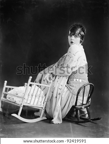 Young woman sitting on a toy chair next to a toy baby crib - stock photo