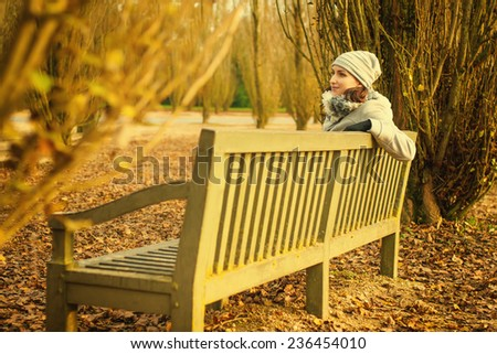 Young woman sitting on a wooden bench in autumn city park
