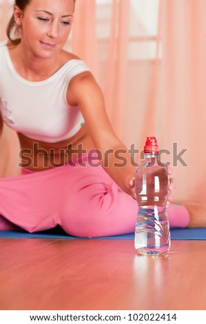 Young woman sitting on a yoga mat and holding bottle of water