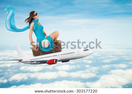 Young woman sitting on airplane, flying above clouds. Concept of traveling - stock photo