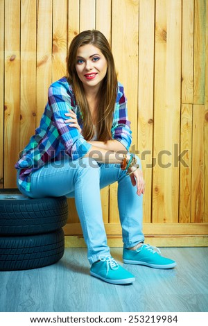 Young woman sitting on auto tires against wooden wall. Smiling model with long hair. Beautiful girl portrait.