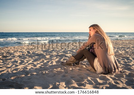 Young Woman sitting On Beach in winter