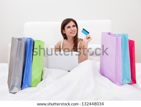 Young Woman Sitting On Bed And Shopping Online - stock photo