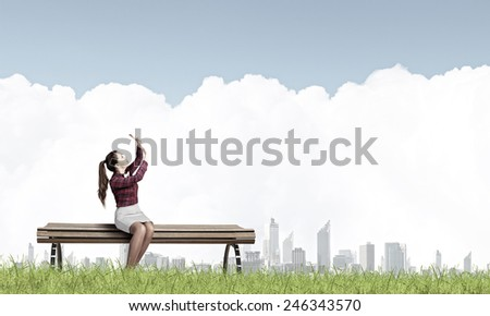 Young woman sitting on bench afraid of something