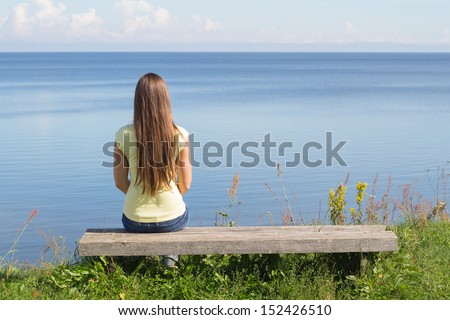 Young woman sitting on bench facing the sea  - stock photo
