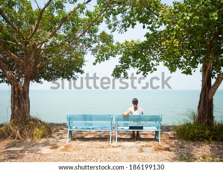 Young woman sitting on bench facing the sea in Thailand - stock photo